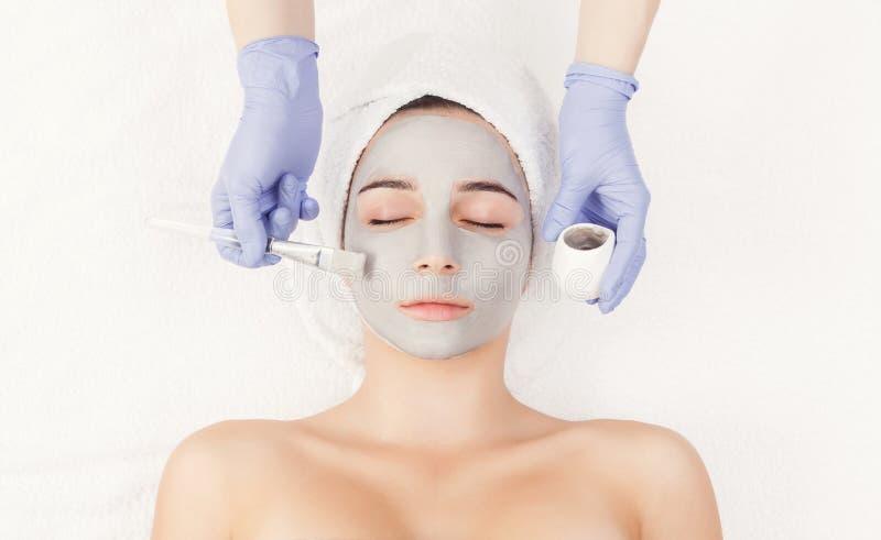 Kvinnan får framsidamaskeringen av kosmetologen på brunnsorten arkivbild