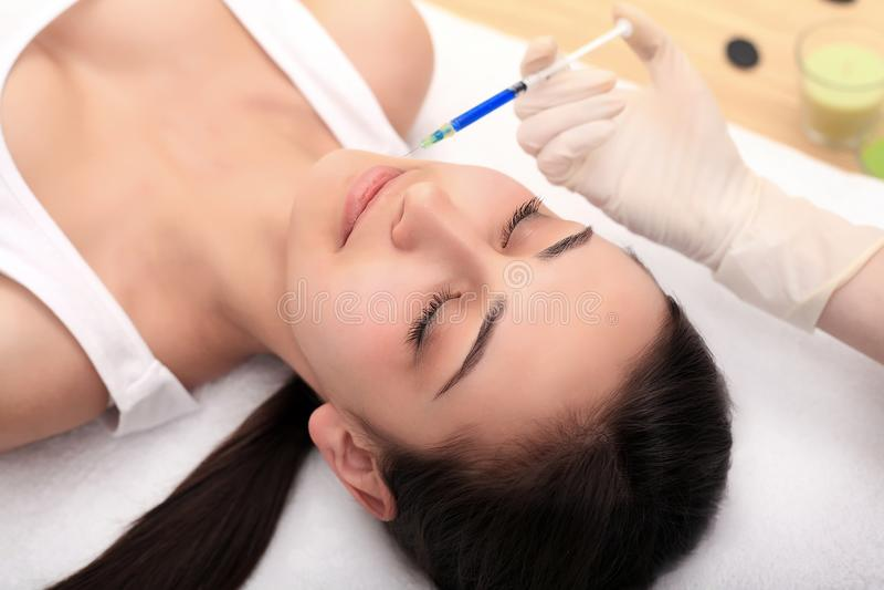 Kvinnan får injektionen i hennes framsida Skönhetkvinna som ger injektioner arkivfoton