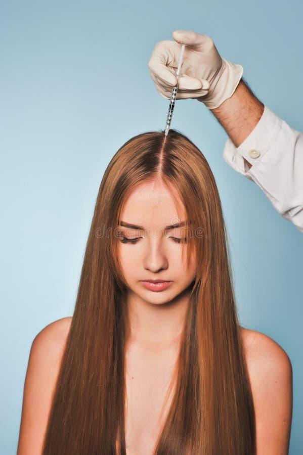 Kvinnan får injektionen i huvud Mesotherapy royaltyfri foto