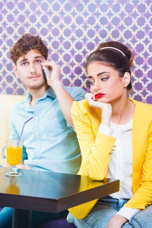Kvinnan får uttråkad, medan hennes datum talar på telefonen arkivfoto