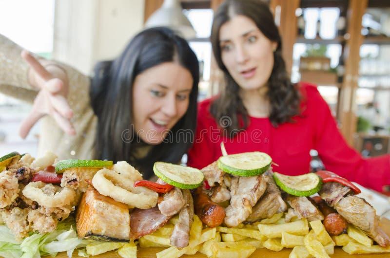 Kvinnan för brunett som två är klar för, äter mycket mat arkivfoton