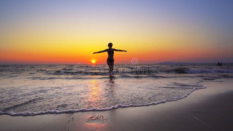 Kvinnan för modemodellen går in i havsolnedgångvatten med den öppna handsneda bollen fotografering för bildbyråer