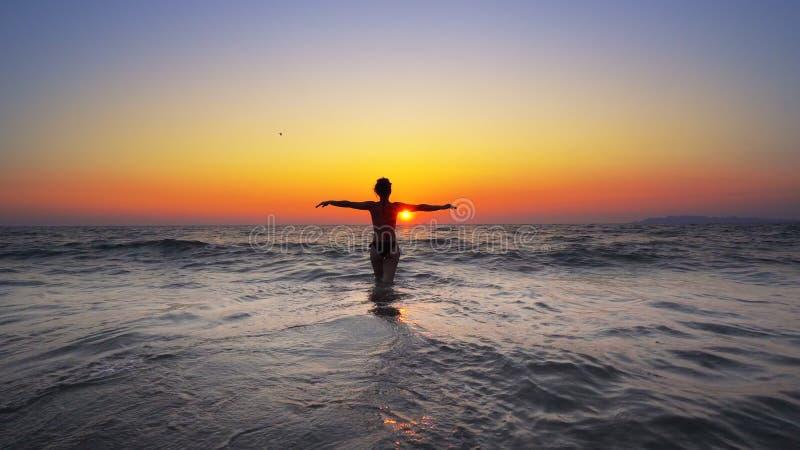 Kvinnan för modemodellen går in i havsolnedgångvatten med den öppna handsneda bollen royaltyfria foton