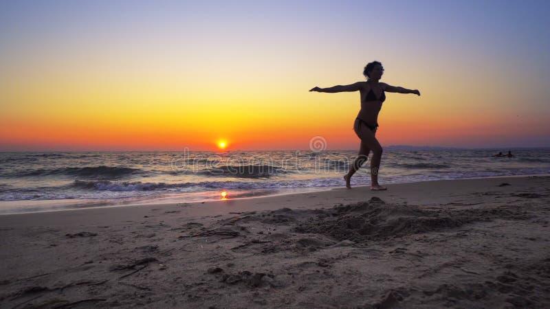 Kvinnan för modemodellen går in i havsolnedgångvatten med den öppna handsneda bollen royaltyfri fotografi