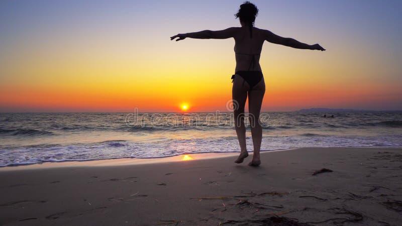 Kvinnan för modemodellen går ut ur havsolnedgångvatten med öppna händer vitt arkivbilder