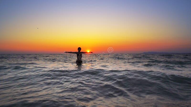 Kvinnan för modemodellen går ut ur havsolnedgångvatten med öppna händer vitt arkivbild