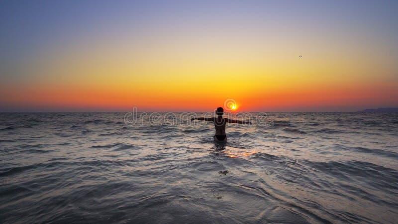 Kvinnan för modemodellen går ut ur havsolnedgångvatten med öppna händer vitt royaltyfri bild