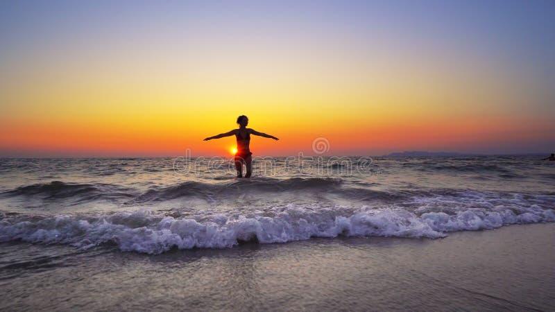 Kvinnan för modemodellen går ut ur havsolnedgångvatten med händer vitt royaltyfri bild