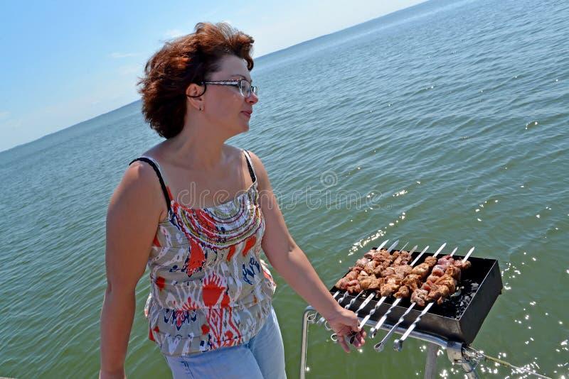 Kvinnan förbereder en kebab på fyrpannan som fixas på en yachthand-stång blå solig russia för tak för daghuskaliningrad region so arkivbilder