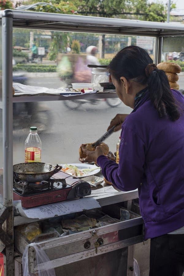 Kvinnan förbereder en smörgås i en gata av Can Tho, Vietnam royaltyfri fotografi