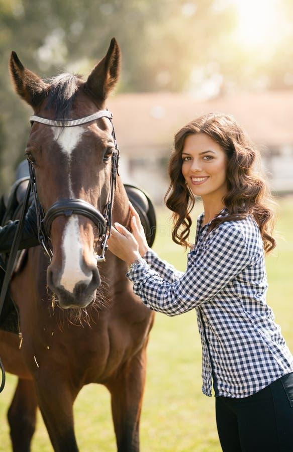 Kvinnan förbereder hennes häst för att rida, mig älskar djurt royaltyfri fotografi