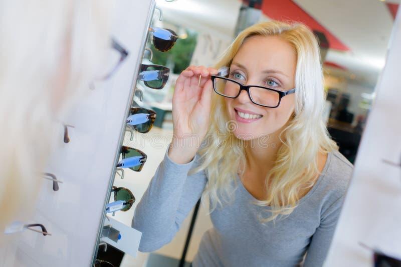 Kvinnan försöker på exponeringsglas för bra vision royaltyfri foto