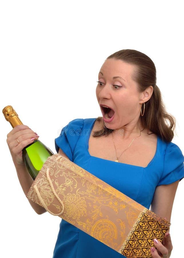 Kvinnan förvånas och tycker om att motta en gåva av dyr champagne royaltyfri bild