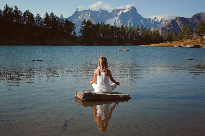 Kvinnan finner fred i bergsjön royaltyfria bilder