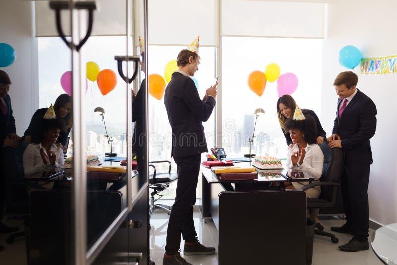 Kvinnan firar födelsedagpartiet i affärskontor med coworkeren royaltyfria foton