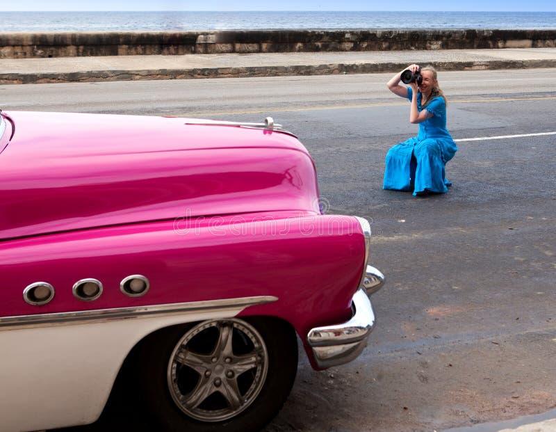 Kvinnan fotograferar den forntida bilen på den Malecon gatan Januari 27, 2013 i gammal havannacigarr, Kuban royaltyfria foton