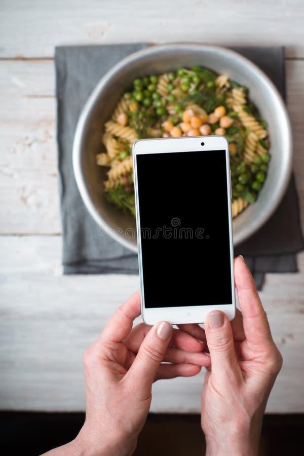 Kvinnan fotograferar en lagad mat sallad royaltyfria bilder