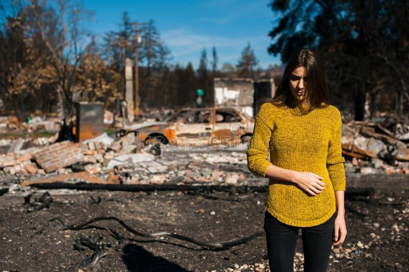 Kvinnan framme av henne brände hem efter brandkatastrof royaltyfri fotografi