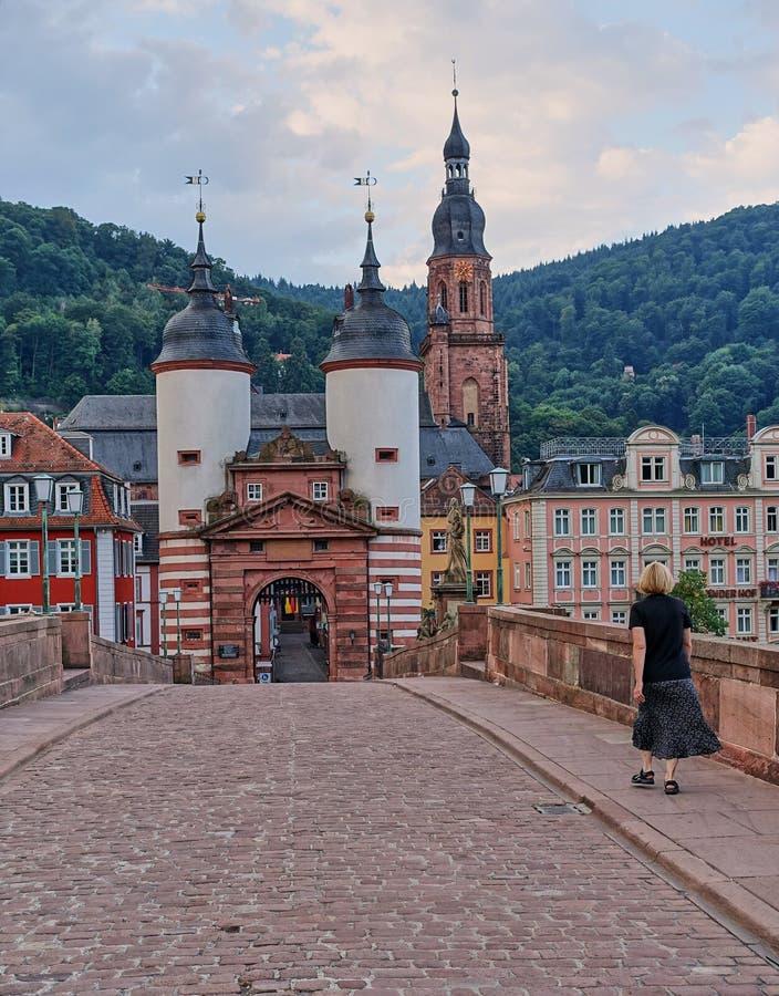 Kvinnan går över den gamla bron i destinationsstad av Heidelberg, Tyskland arkivbild