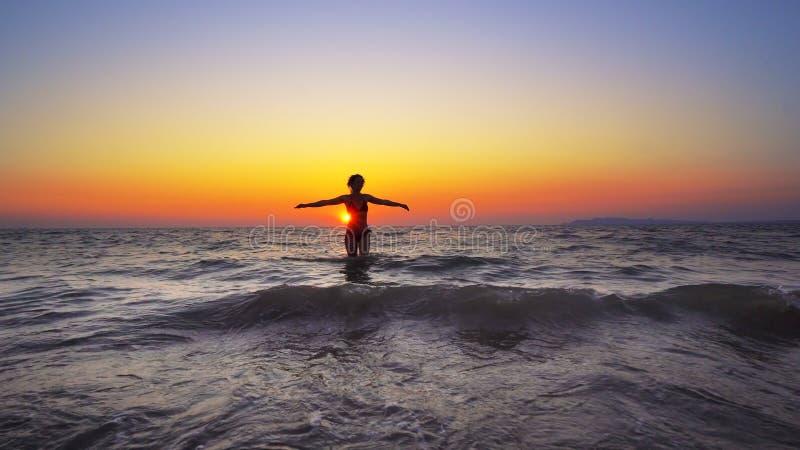 kvinnan går in i havsolnedgångvatten med den öppna handsneda bollen, FRIHETSBEGREPP arkivfoton