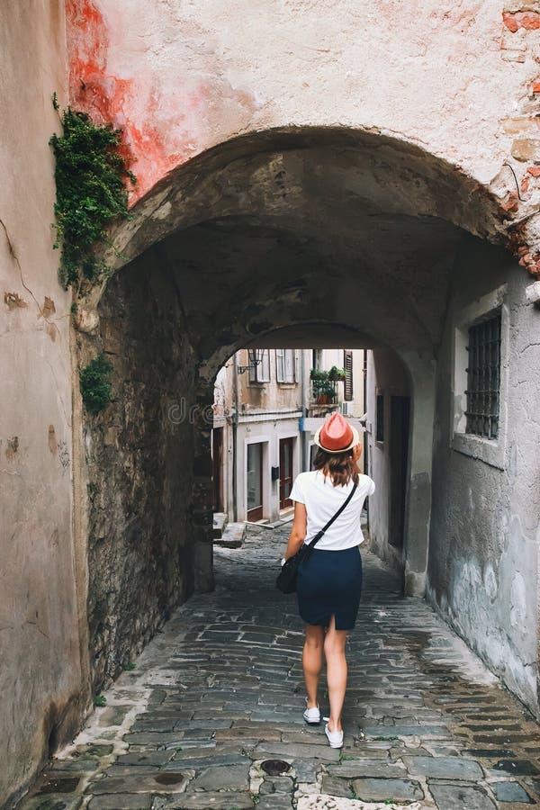 Kvinnan går på de historiska europeiska gatorna av den gamla staden royaltyfri fotografi
