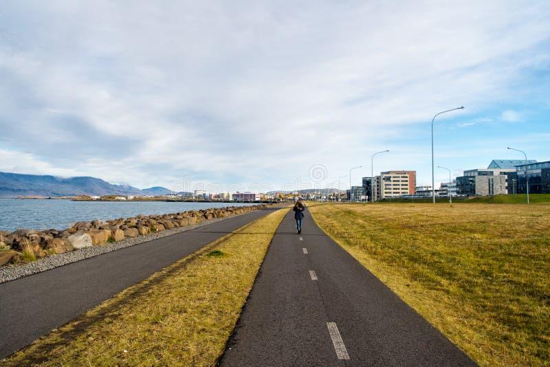Kvinnan går på vägen längs havet på molnig himmel i reykjavik, Island Promenad på sjösidan på cityscape Lopp och reslust på urba royaltyfria foton