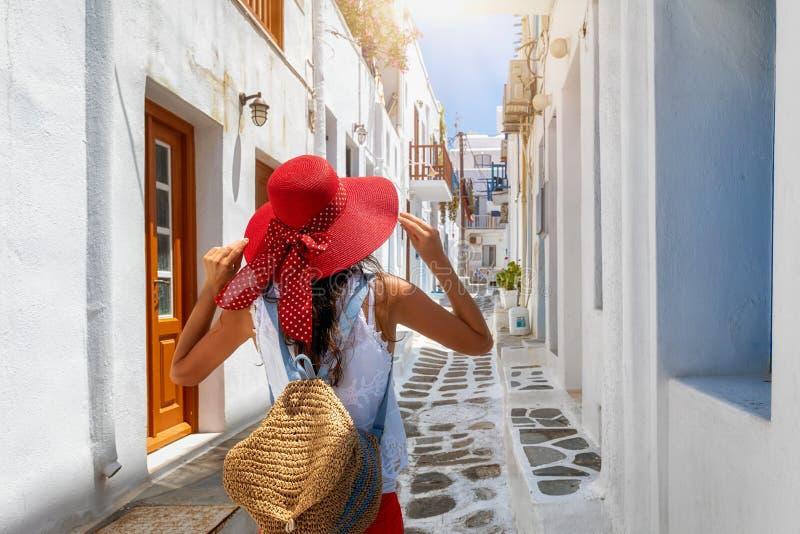 Kvinnan går till och med gränderna av den Mykonos staden, Cyclades, Grekland arkivfoton
