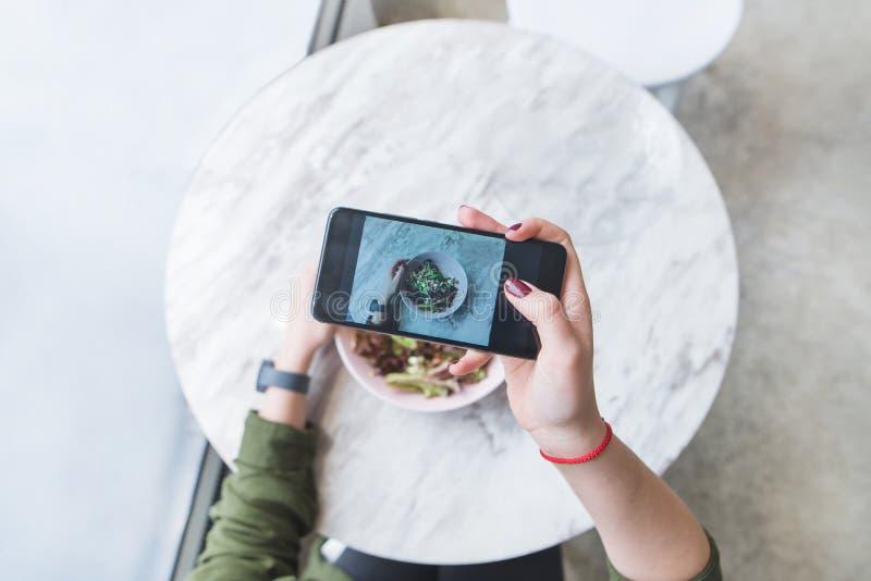 kvinnan gör ett foto av hennes mat på restaurangen på tabellen Bloggeren väljer upp en sallad på tabellen arkivbild