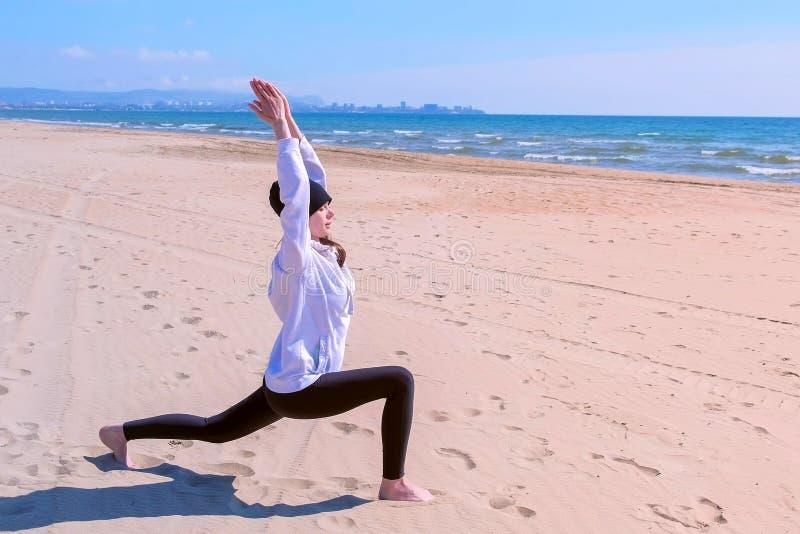 Kvinnan gör hög lunch poserar på övning för sport för utbildning för yoga för havssandstrand royaltyfria foton