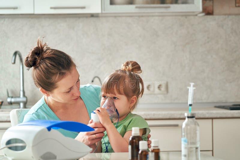 Kvinnan gör inandning till ett barn hemma kommer med nebulizermaskeringen till hans framsida inhalerar dunsten av läkarbehandling arkivfoto