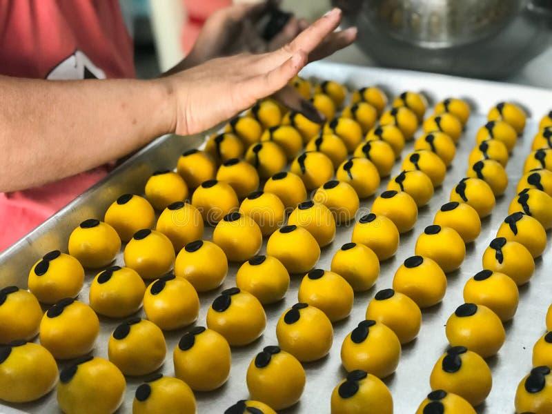 Kvinnan gör kakor som stoppas med ananas arkivbilder