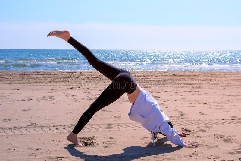 Kvinnan gör nedåtriktat - fasadbeklädnadhunden poserar i yoga på övning för sport för havssandstrand royaltyfri foto