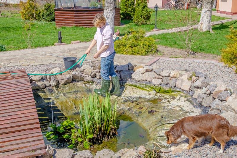 Kvinnan gör på våren ren det konstgjorda dammet royaltyfria bilder