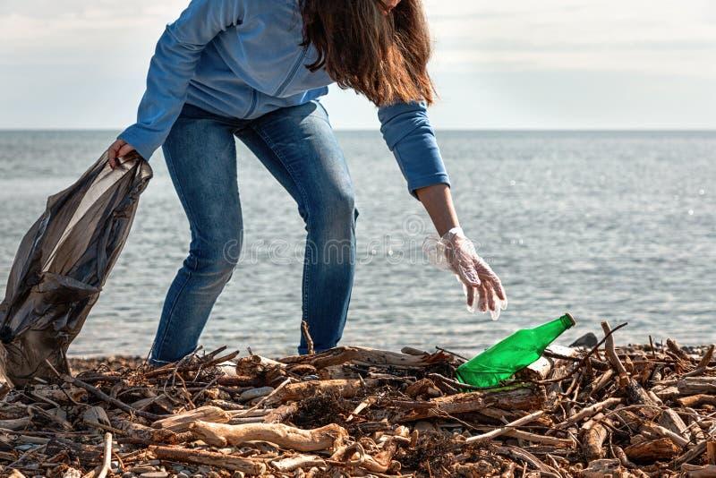 Kvinnan gör ren avskräde på stranden, väljer upp flaskan Ekologi jorddag, rengöra av territoriumbegreppet arkivbild