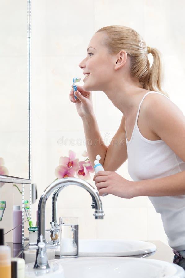 Kvinnan gör ren hennes tänder royaltyfri fotografi