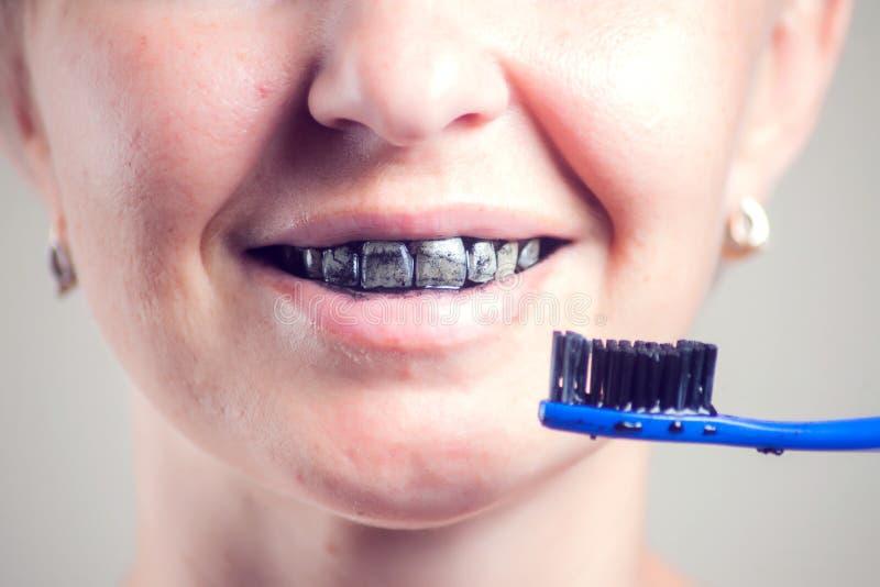 Kvinnan gör ren hennes tänder med koltandkräm Folk och sjukv?rdbegrepp royaltyfria foton