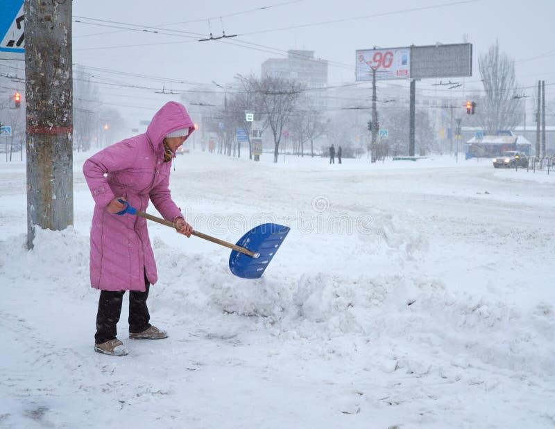 Kvinnan gör ren snön på gatan för th e fotografering för bildbyråer