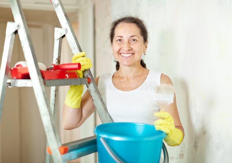 Kvinnan gör reparationer i lägenhet arkivbild