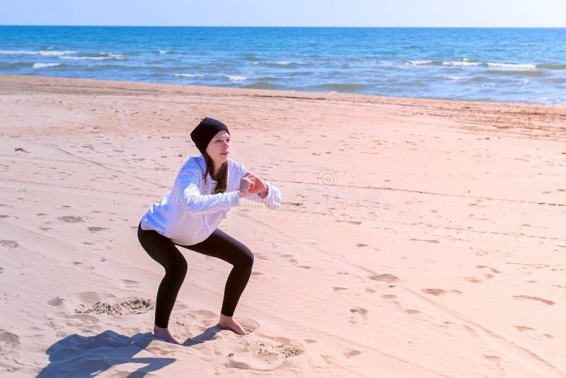 Kvinnan gör squats på övningar för utomhus- sport för kondition för havssandstrand på utbildning arkivfoto