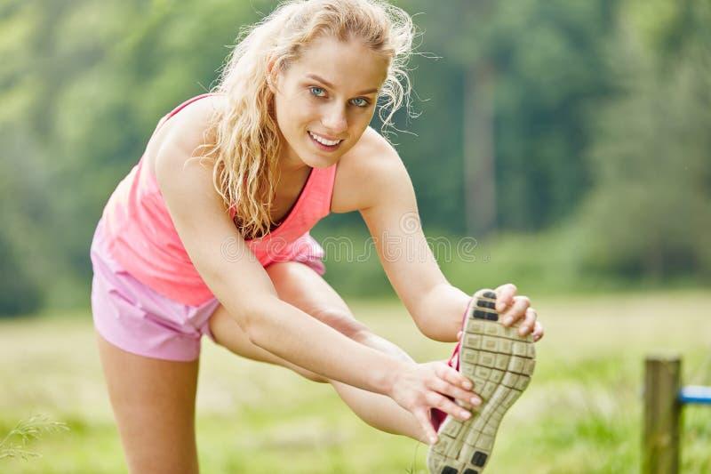 Kvinnan gör sund sträckande övning arkivfoto