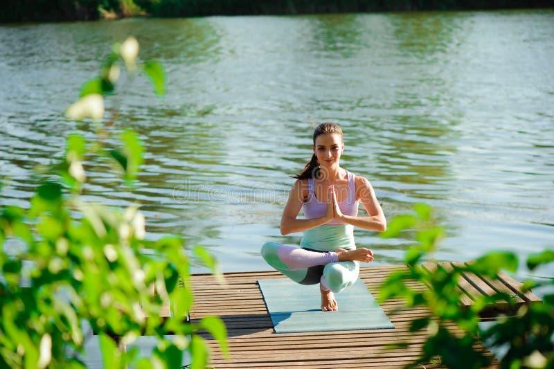 Kvinnan gör utomhus- yoga Öva för kvinna som är livsviktigt, och meditation för konditionlivsstilklubba på naturbakgrunden arkivfoton