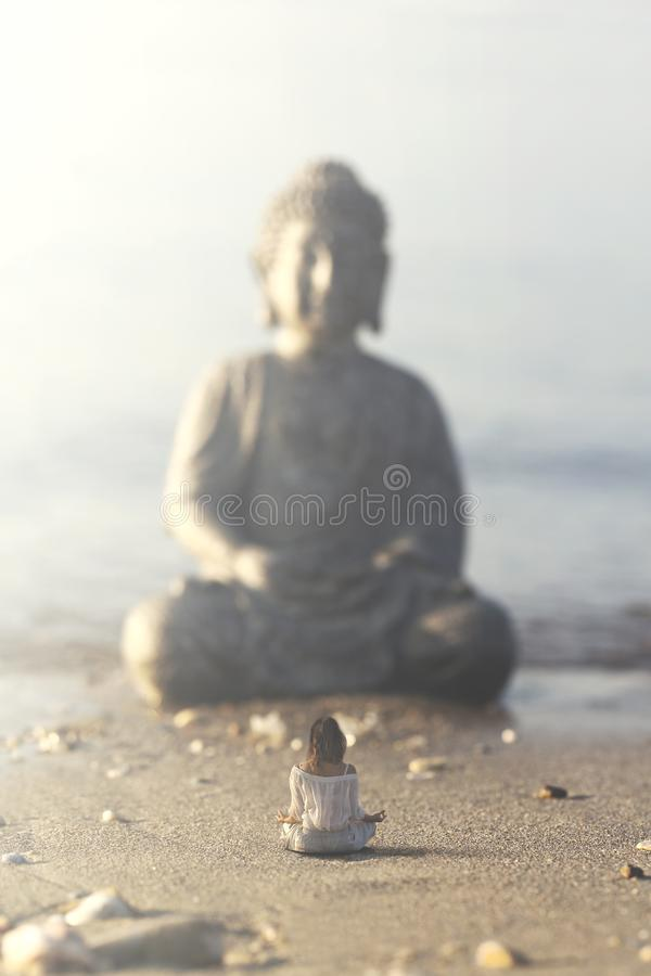 Kvinnan gör yogaövningar framme av Buddhastatyn arkivfoto
