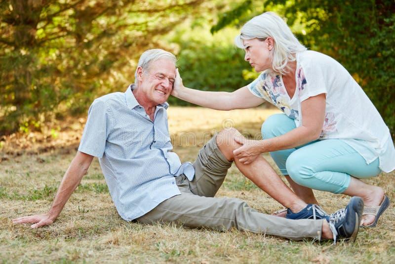 Kvinnan ger första hjälpen till en man och tröstar honom royaltyfri fotografi