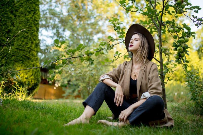 Kvinnan har att koppla av i en trädgård nära ungt äppleträd royaltyfria bilder