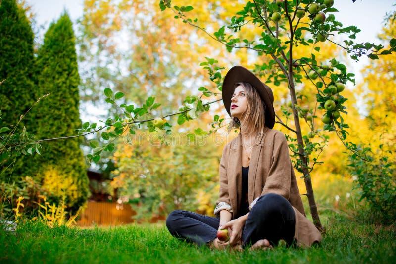Kvinnan har att koppla av i en trädgård nära ungt äppleträd arkivbild