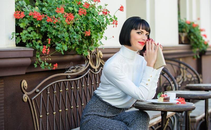 Kvinnan har drinken att tycka om att l?sa Bibelnkaf?terrassen Modern litteratur f?r kvinnlig Kaffe och Bibeln f arkivbilder