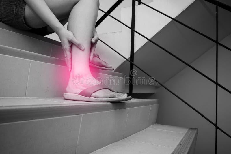Kvinnan har kalvkrampen, och trycka p? det gjorde ont benet under g? ner trappa Svartvit signal med den röda fläcken på hennes be arkivbilder