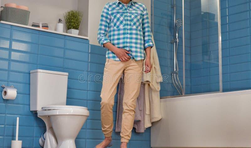 Kvinnan har smärtar i den lägre magen i toaletten fotografering för bildbyråer
