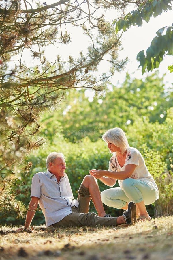 Kvinnan hjälper den höga mannen med knäskadan arkivfoto