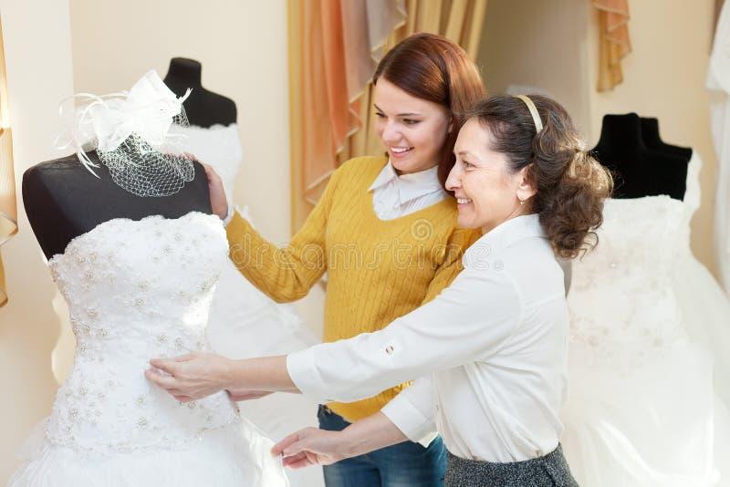 Kvinnan hjälper gitlen, i att välja den brud- kappan royaltyfri fotografi